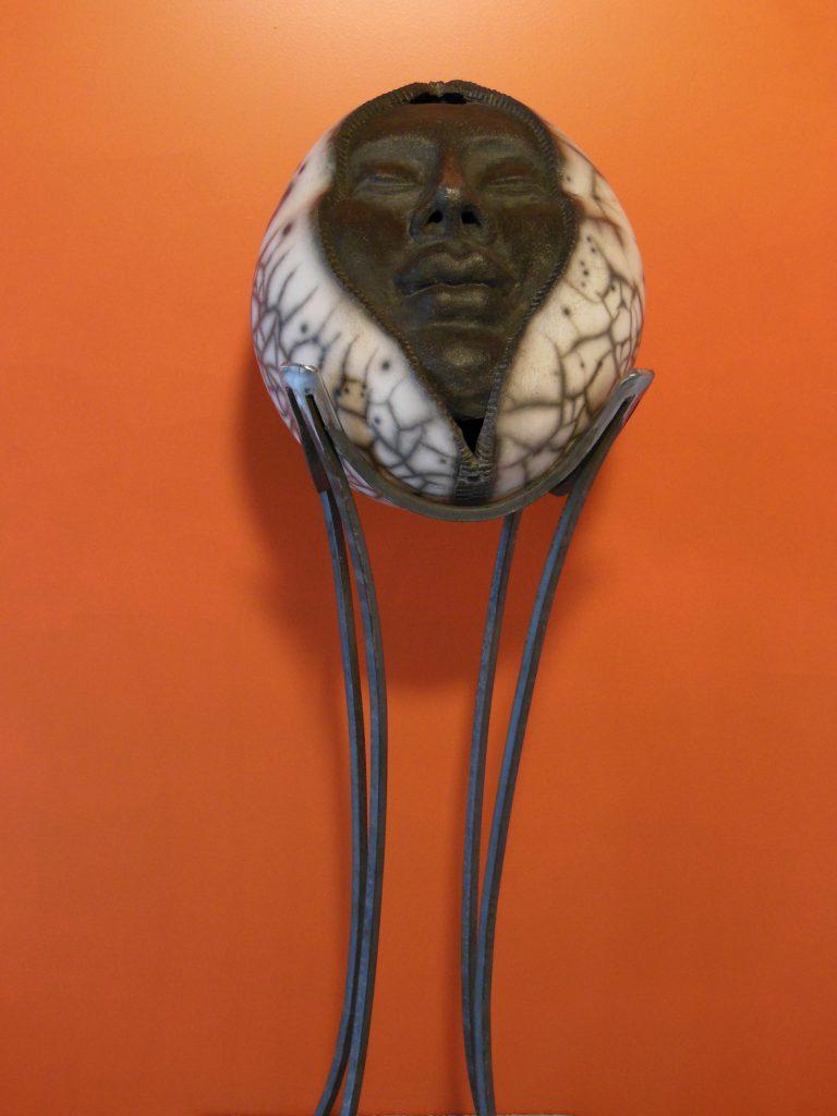 Visage intégré dans une sphère en raku et sur son support en ferronnerie