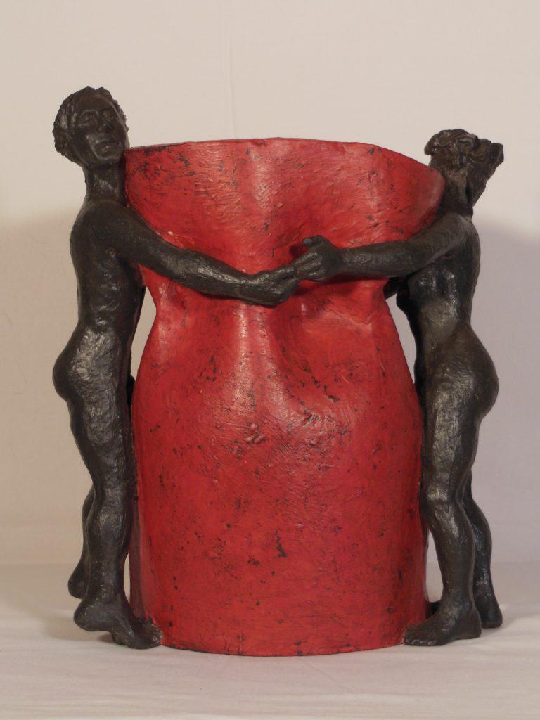 Vase rouge et noir entouré d'un homme et d'une femme